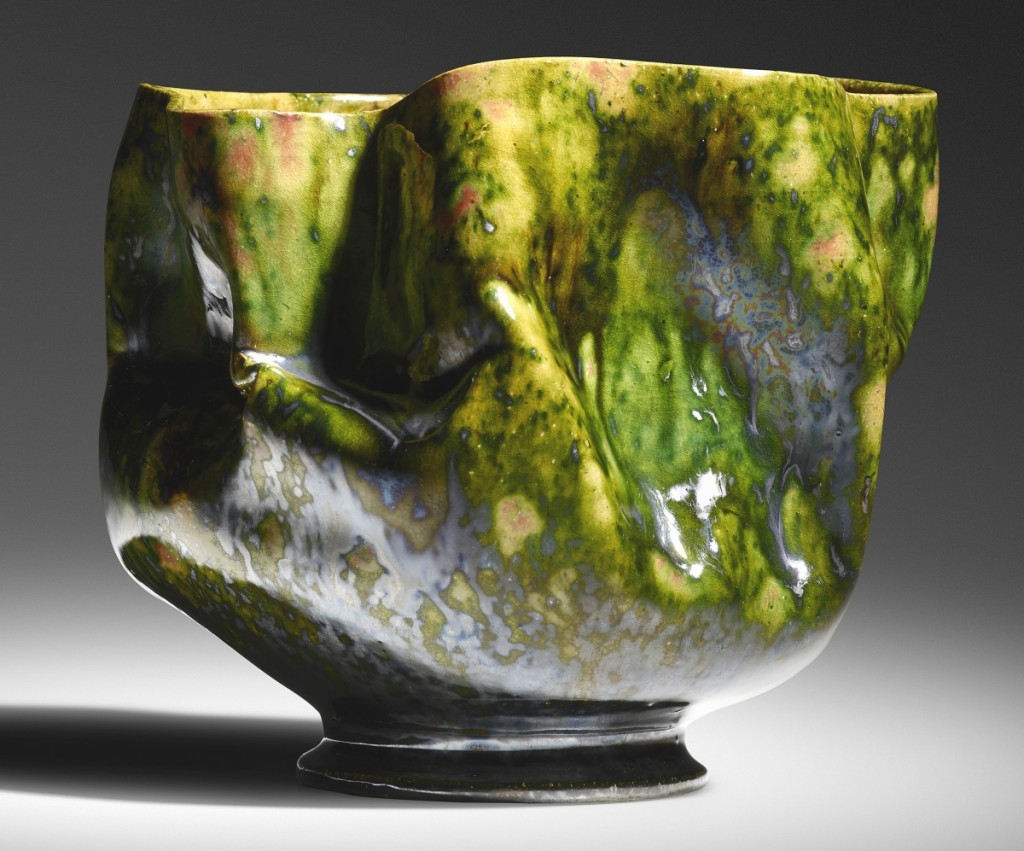 """From an extensive run of pieces by the """"Mad Potter of Biloxi"""" George Ohr, the top selling piece, at $62,500, went to this large vase, 1897-1900, 5½ inches high by 6½ inches wide, featuring Ohr's trademark in-body manipulations and sporting green, gunmetal and raspberry glazes with a yellow interior."""