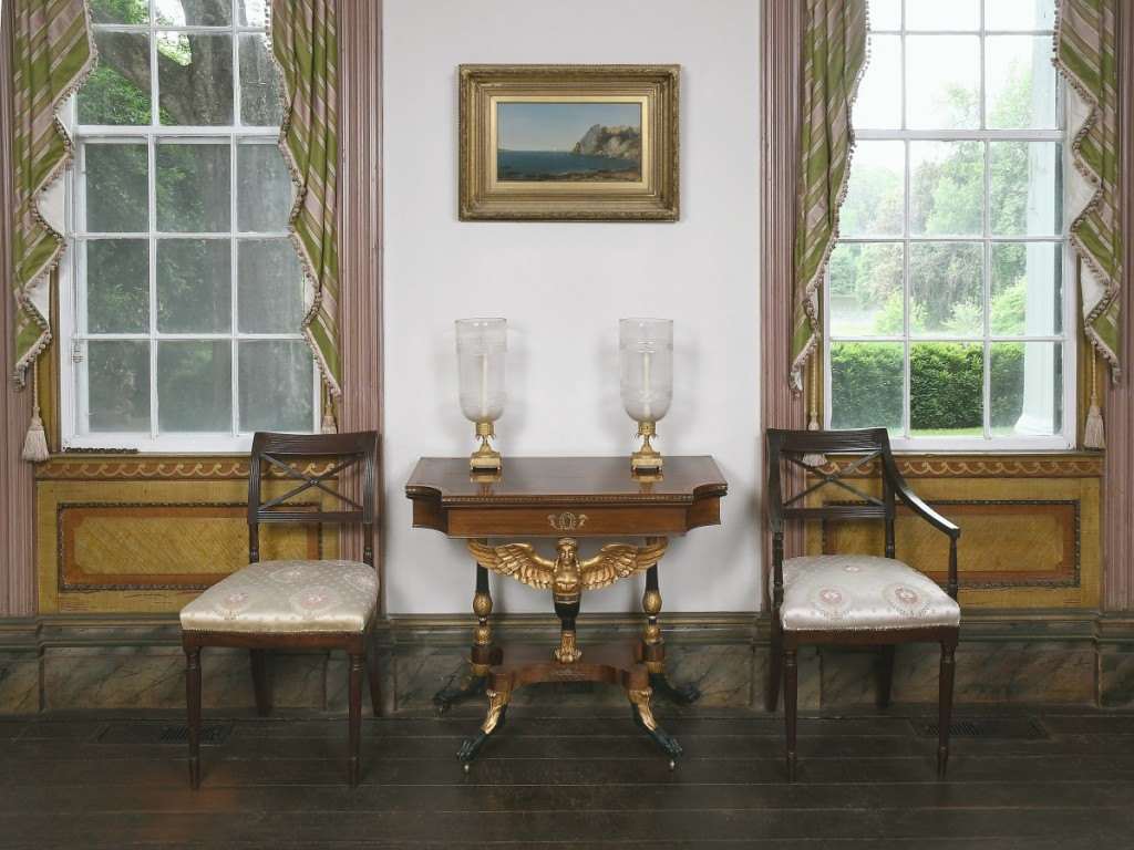 """Here, in a photo staged by Brunk Auctions at Bankshaven, two Federal chairs flank the swivel-top card table possibly made by 1815-1820. Above hangs the 1856 oil on canvas """"Beacon Rock, Newport"""" by John Frederick Kensett."""