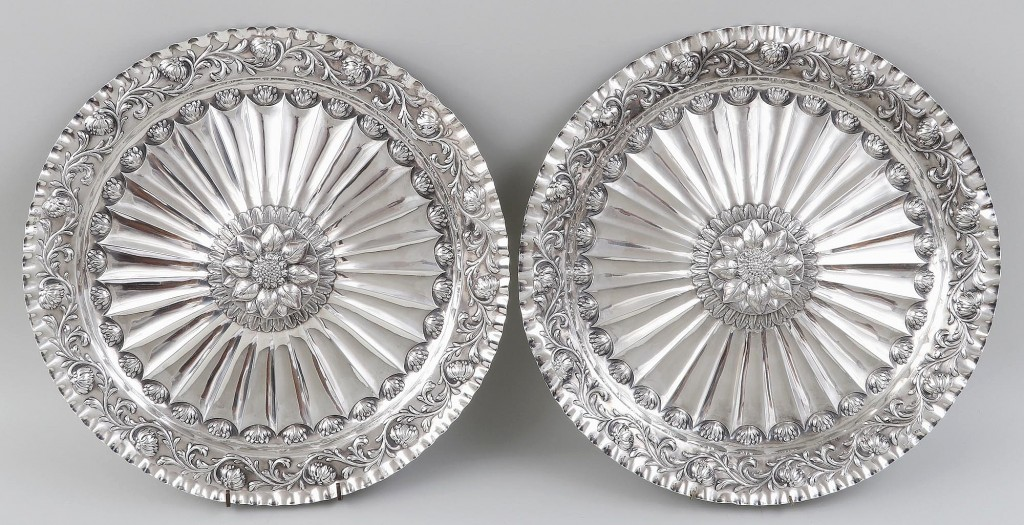 This pair of large Eighteenth Century English sterling silver sideboard chargers with scalloped edges, floral repousse and sunflower centers commanded $4,200.