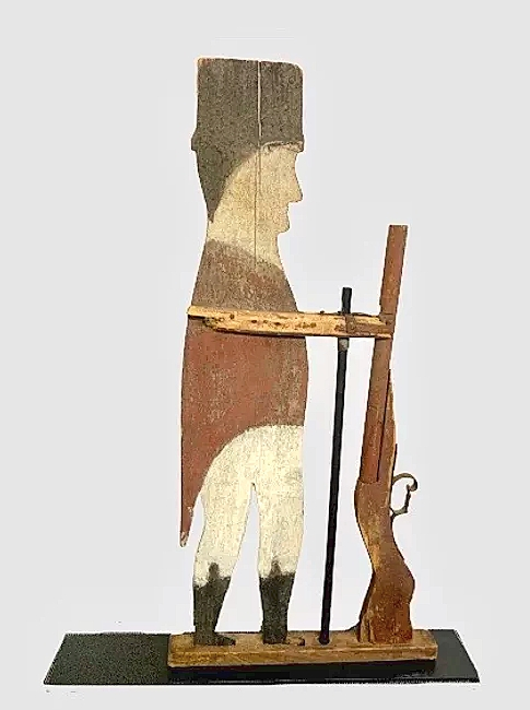 Paul and Connie Polce of Ponzi's Antiques offered this early Twentieth Century wooden folk art soldier weathervane. The soldier was from the War of 1812 and held his rifle with a pocket watch hanging from his pocket on the opposite side. It measures 32 inches tall.
