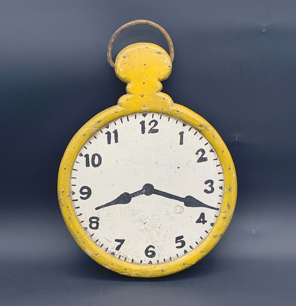 A wooden pocket watch trade sign from the early Twentieth Century with yellow painted wooden case and white and black painted dial connected with a buyer. Measuring 16 by 11 inches and in untouched original condition, it was offered by Mary & Joshua Steenburgh.