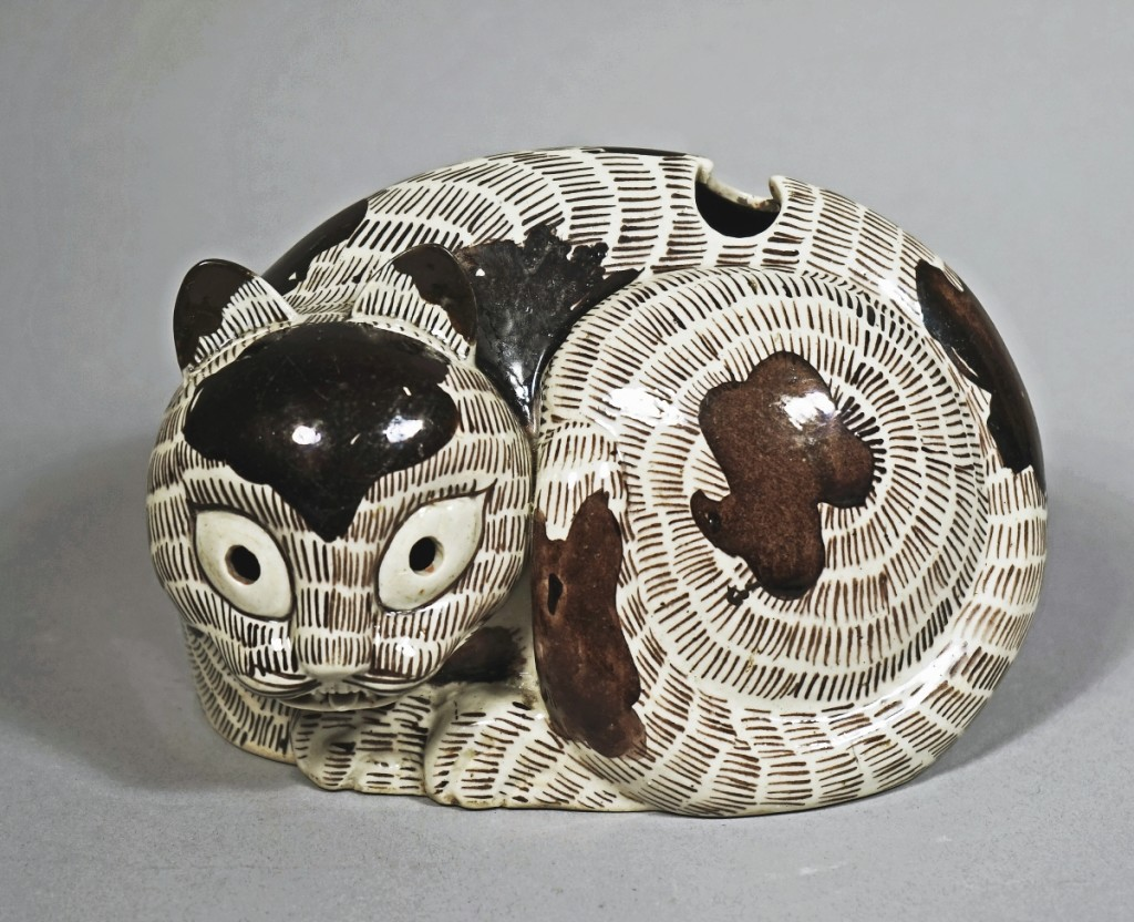 Sepia and aubergine glazed porcelain cat night lamp, China, Kangxi period, AD 1662-1722. Ralph M. Chait Galleries.
