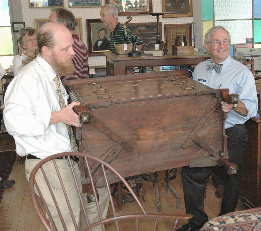 Weekly educational forums bring people in the shop during the spring and fall. Here, Kevin and Arthur hoist a chest of drawers from Litchfield County, Conn., giving guests a view of its distinctive, cross-braced construction.