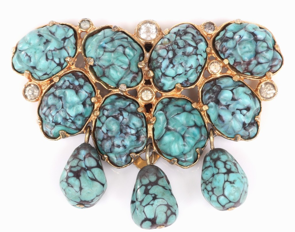 Hastings related she was unsure of the faux turquoise glass on this piece and others in the sale, but she grew to adore it. Bidders liked this brooch for its contrast with the glass and the gold pot metal backing as it went on to sell for $2,000 on a $300 estimate. An identical form with emerald green glass stones did better at $2,375.