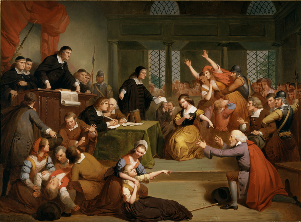 """Curators described this painting on the wall placard, """"Tompkins Harrison Matteson summarizes in one scene a number of dramatic incidents that occurred during the days of George Jacobs Sr's examination and trial. Most of the action focuses on the dramatic moment when his own granddaughter, Margaret, testified against him. Placed in the center of the painting, she kneels and points her finger directly at her grandfather, who responds by pleading his innocence with upraised arms. The other dominant figure, the woman lunging forward, may represent Margaret's mother, Rebecca, who was also arrested. The judge standing before Margaret holds a letter in one hand while pointing with the other to documents on the clerk's table. This gesture might reference the letter Margaret gave the court recanting her earlier testimony, which came too late to save her grandfather from the gallows."""" """"Trial of George Jacobs, Sr. for Witchcraft"""" by Tompkins Harrison Matteson (New York, 1813-1884), 1855. Oil on canvas. Gift of R.W. Ropes, 1859."""
