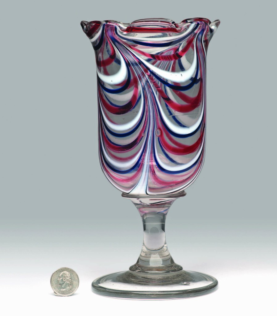 A trumpet-form free-blown vase, 1860-80, was colorless, but was alive with red, white and blue loopings. It brought $3,218.