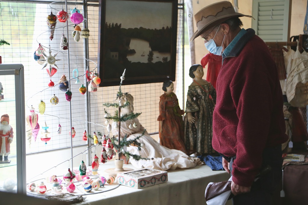 A buyer looks through the assortment of Christmas ornaments at Blue Dog Antiques, Stafford Springs, Conn. —Black River Antique Show