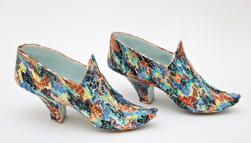 """Costume and antique textiles were offered from Cora Ginsburg, Sharon, Conn., and New York City, a first time exhibitor at the Deerfield show. Among the works was this fanciful pair of Delftware shoes, circa 1750-70. The gallery wrote, """"Miniature shoes are among the most quintessential wares produced in Delft in the Seventeenth and Eighteenth Centuries, where they would be purchased on the occasion of a betrothal or given as a token of affection between friends or lovers."""""""