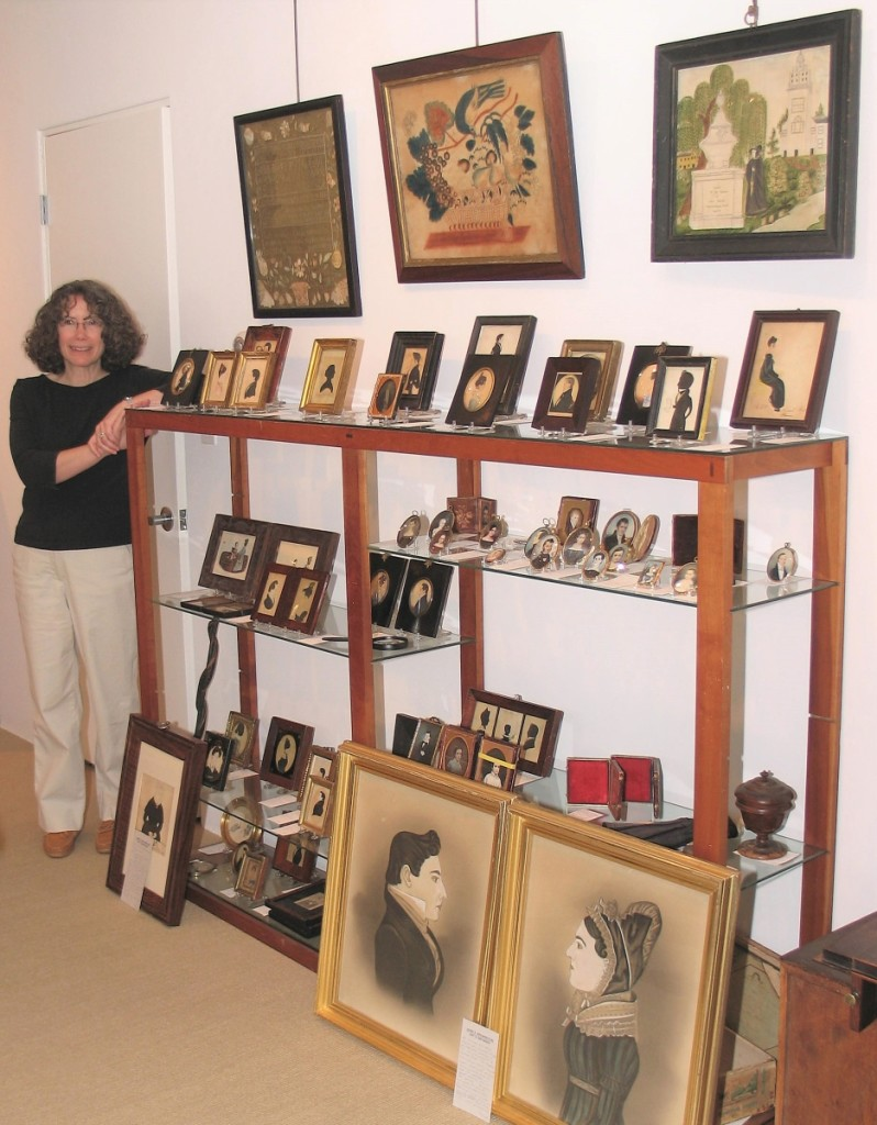 Joan stands next to a collection of small-scale and miniature folk art portraits.
