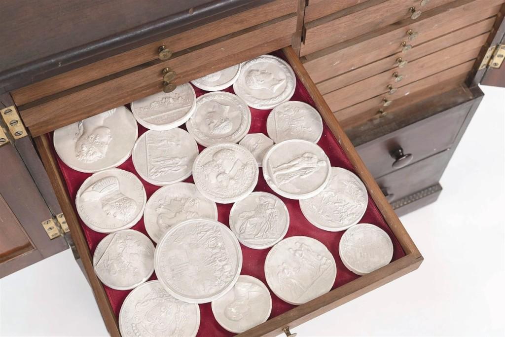Grand Tour plaster intaglios in an English mahogany veneer cabinet were bid to $2,875.