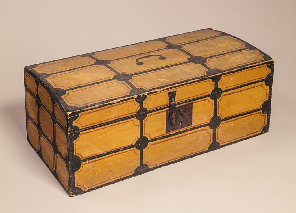 """Offered from Frank and Barbara Pollack American Antiques & Art, Highland Park, Ill., was this paint-decorated box, 24 inches long, attributed to Salmon Brewster (1802-1887) of Leeds, Maine. The decoration simulates a paneled trunk and features a faux painted bale handle on the lid. Pollack called it """"the best of Maine in untouched original condition,"""" and it is still available."""