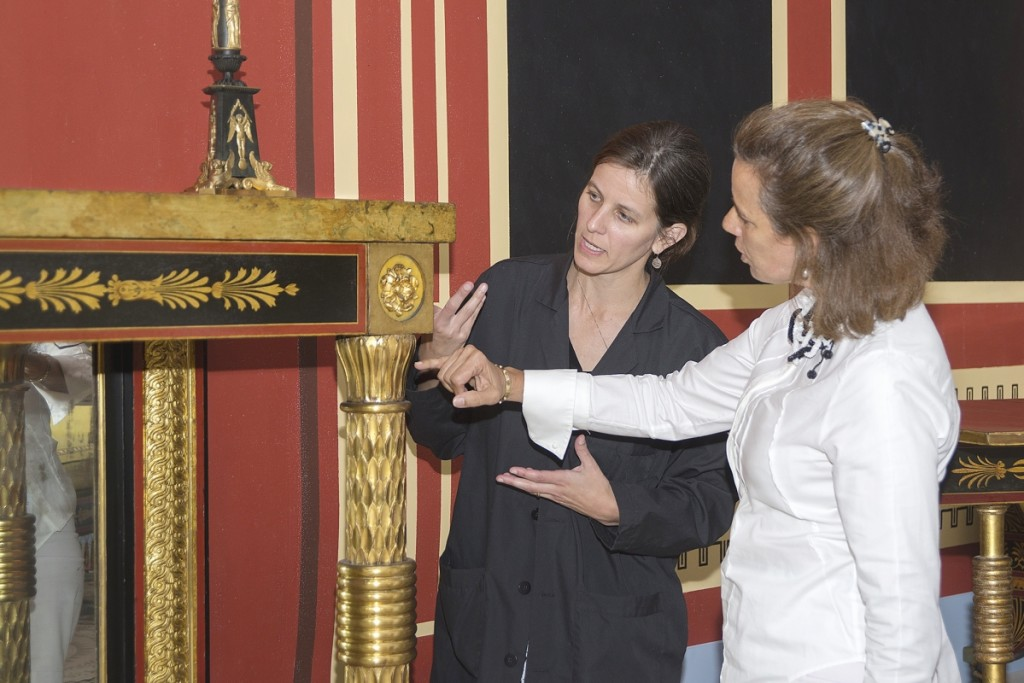 "Alexandra Kirtley, right, and Peggy A. Olley, the PMA's associate conservator of furniture and woodwork, examine a sideboard designed by Benjamin Latrobe and made by John Aitken for Philadelphians William and Mary Waln. Kirtley and Olley collaborated on the book and exhibition ""Classical Splendor: Painted Furniture for a Grand Philadelphia House."""