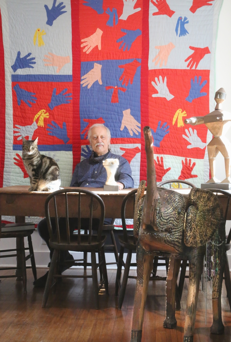 """Aarne Anton and his cat sit at the dining table in their Pomona, N.Y., home. Behind is a quilt by Sarah Mary Taylor, """"Hands and Angels."""" On the table at right is a copper man that was once in the collection of Estelle Freedman. In the foreground is an elephant from OL Samuels, which the artist used as a valuables safe."""