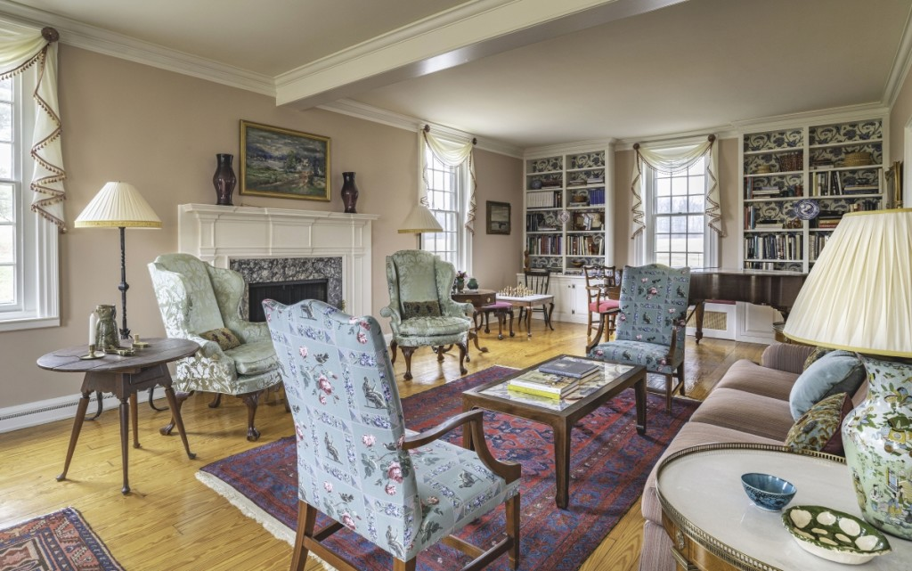 """I wanted the living room at Chandler Farm to be as suitable for the Cadou children as for a cocktail party,"" says Jayne, who combined family furniture with study objects and reproductions that had been scattered around the estate. Cadou salvaged the discarded green silk on the wing chairs from a previous project. Photo James Schneck."