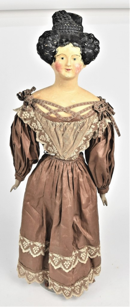 A German papier mache shoulder head doll, circa 1840s, went out at $5,220. The auction house said it had its original glazed brown cotton gown with embroidered lace trim and original undergarment. Dingus collection.