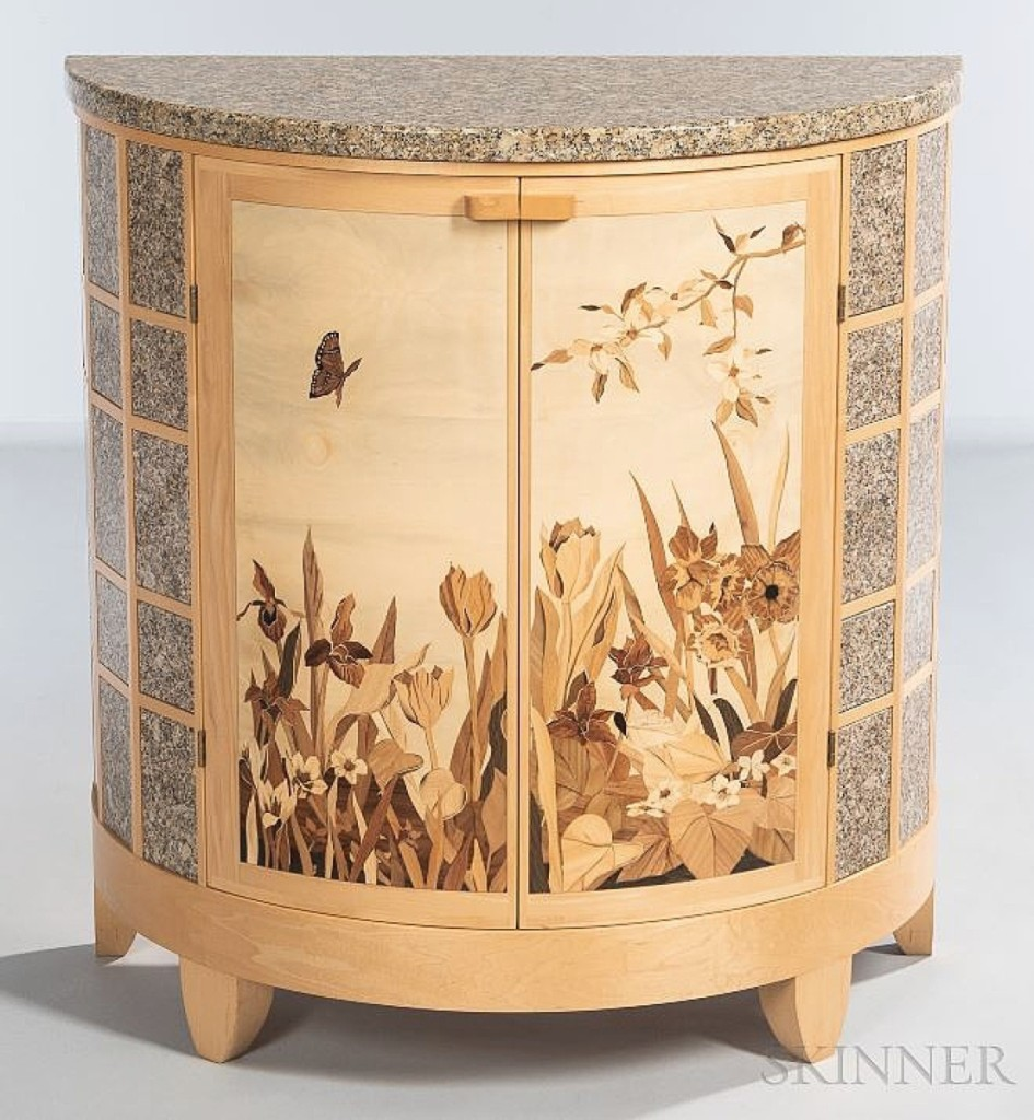 Contemporary studio furniture maker Silas Kopf was the recipient of a 1988 Craftsman's Fellowship from the National Endowment for the Arts, which he used to study traditional marquetry methods at the École Boulle in Paris with Pierre Ramond. This demilune cabinet features a marble top and side panels surrounding a natural scene of flora and a flying butterfly. The circa 2010 example, in maple, holly and other woods, brought $16,250.