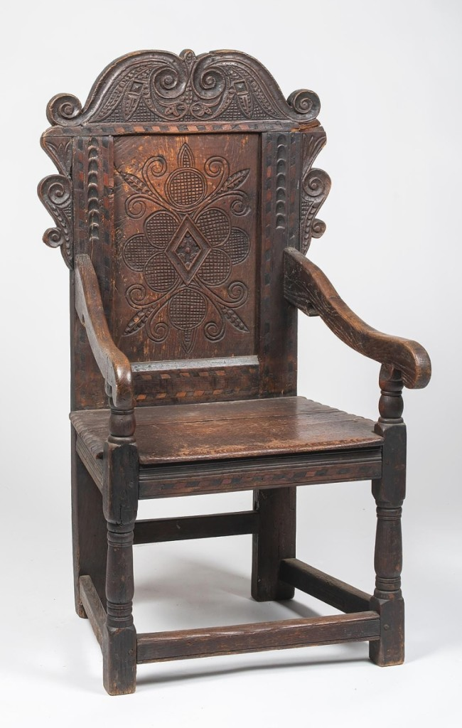 Realizing $3,360 was an English oak Jacobean wainscot armchair with a heavily carved back panel, a two-board plank seat and a box stretcher base.