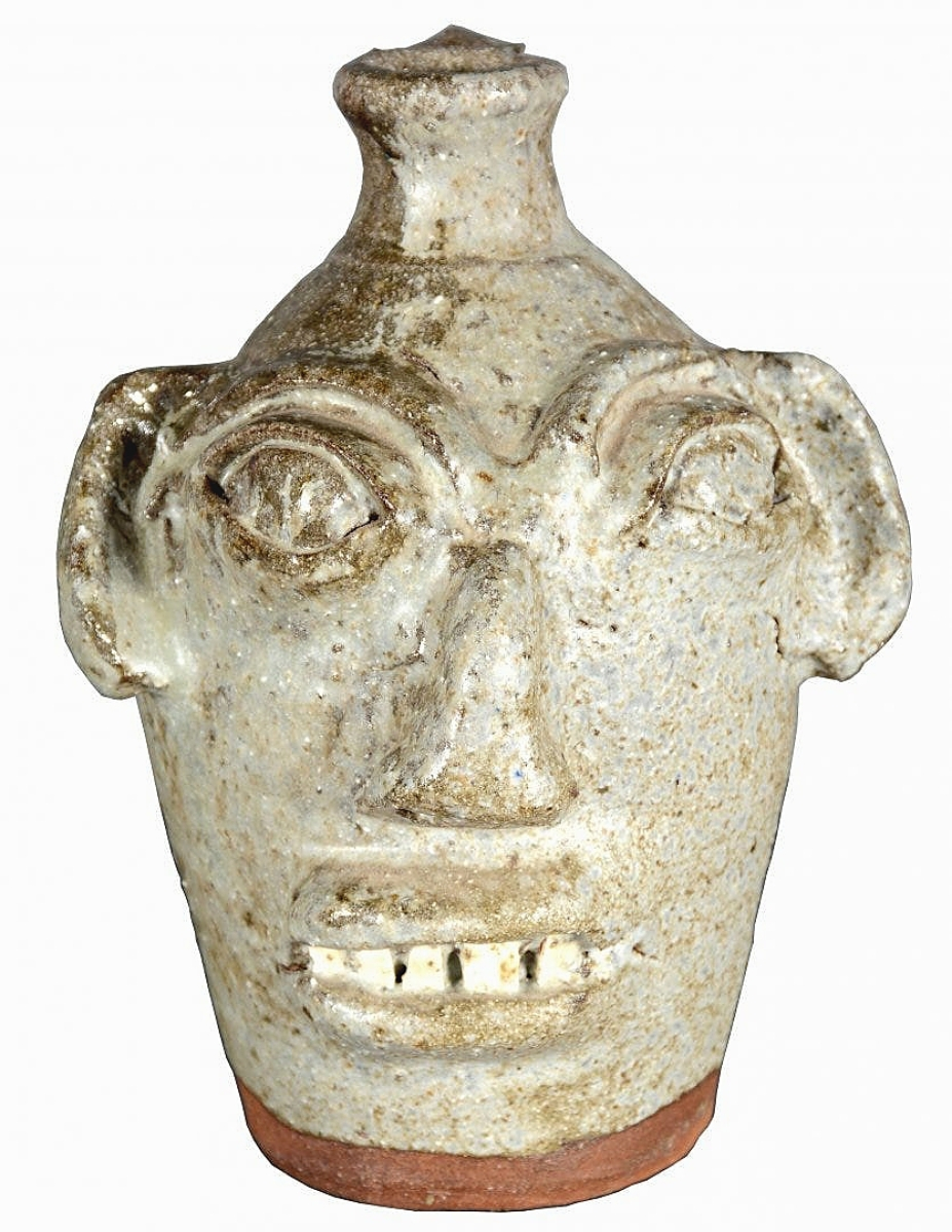 An underfired white/gray glaze pushed interest on a face jug by Burlon Craig. It brought $1,625 on a $500 high estimate.