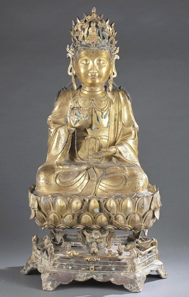 A large Chinese three-piece gilt-bronze guanyin, late Ming/early to mid-Qing dynasty, also performed well, bringing $57,150. Seated in double lotus position (dhyanasana) with the left hand held in dhyana mudra and the right in karana mudra, the guanyin wears a long flowing robe and dhoti bordered with stylized flowers with the chest open draped with an elaborate necklace with hardstone inlay.