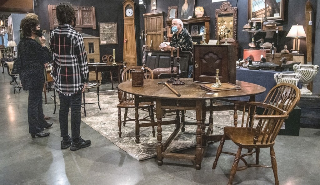 Ray Mongenas discusses some of his furniture with prospective buyers..