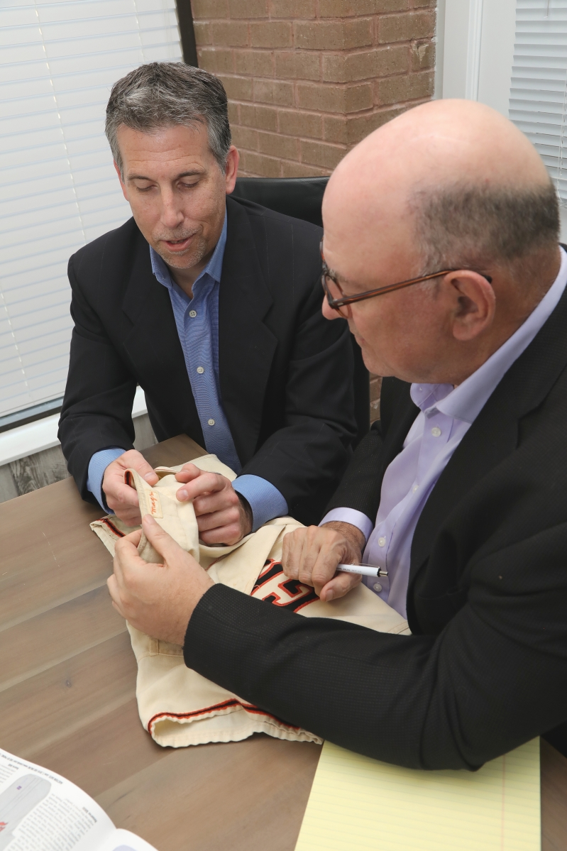 Left, Mike Heffner, president, with the founder   of Lelands.com, the late Josh Evans (right)   examining a Willie Mays game-used jersey.