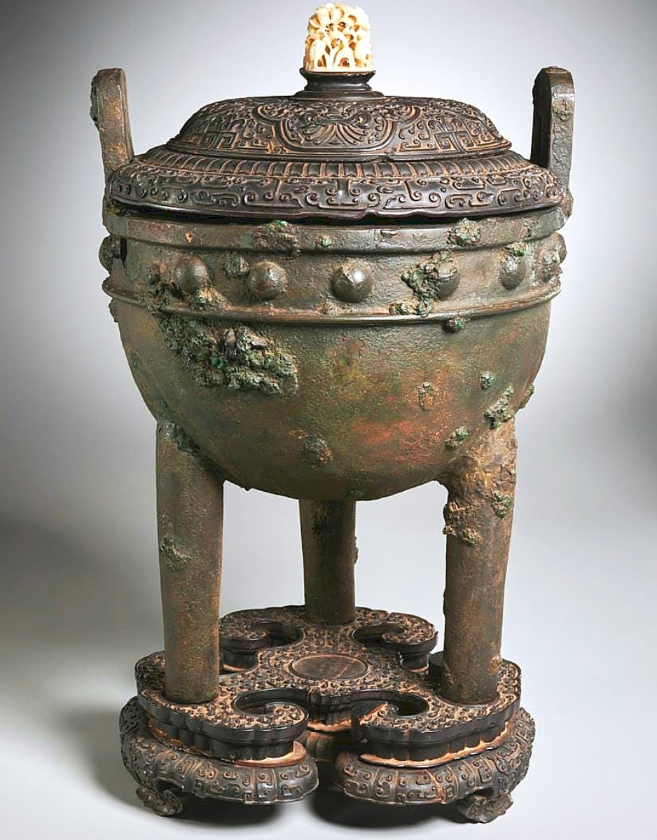 A Chinese archaic-style ritual Ding tripod vessel, 24 inches high, possibly Western Zhou dynasty (Tenth Century BCE), sold for $90,625. The vessel's patinated metal bowl, bell-shaped body with studded rim and upright loop handles on round tapering legs, was on an elaborately carved zitan base and its cover was set with a pierced carved yuan-style white jade finial.