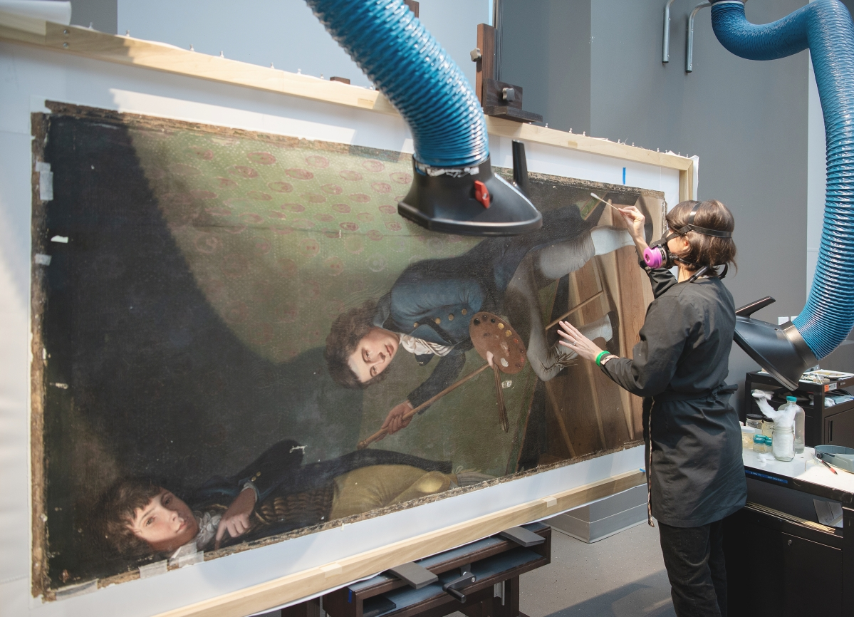 "Lucia Bay, the Joan and John Thalheimer associate conservator of paintings, removes old varnish from the surface of ""Staircase Group (Portrait of Raphaelle Peale and Titian Ramsay Peale I)"" by Charles Willson Peale, 1795. Oil on canvas. The George W. Elkins Collection, 1945. Image courtesy of Philadelphia Museum of Art, 2021. Photo by Jason Wierzbicki."