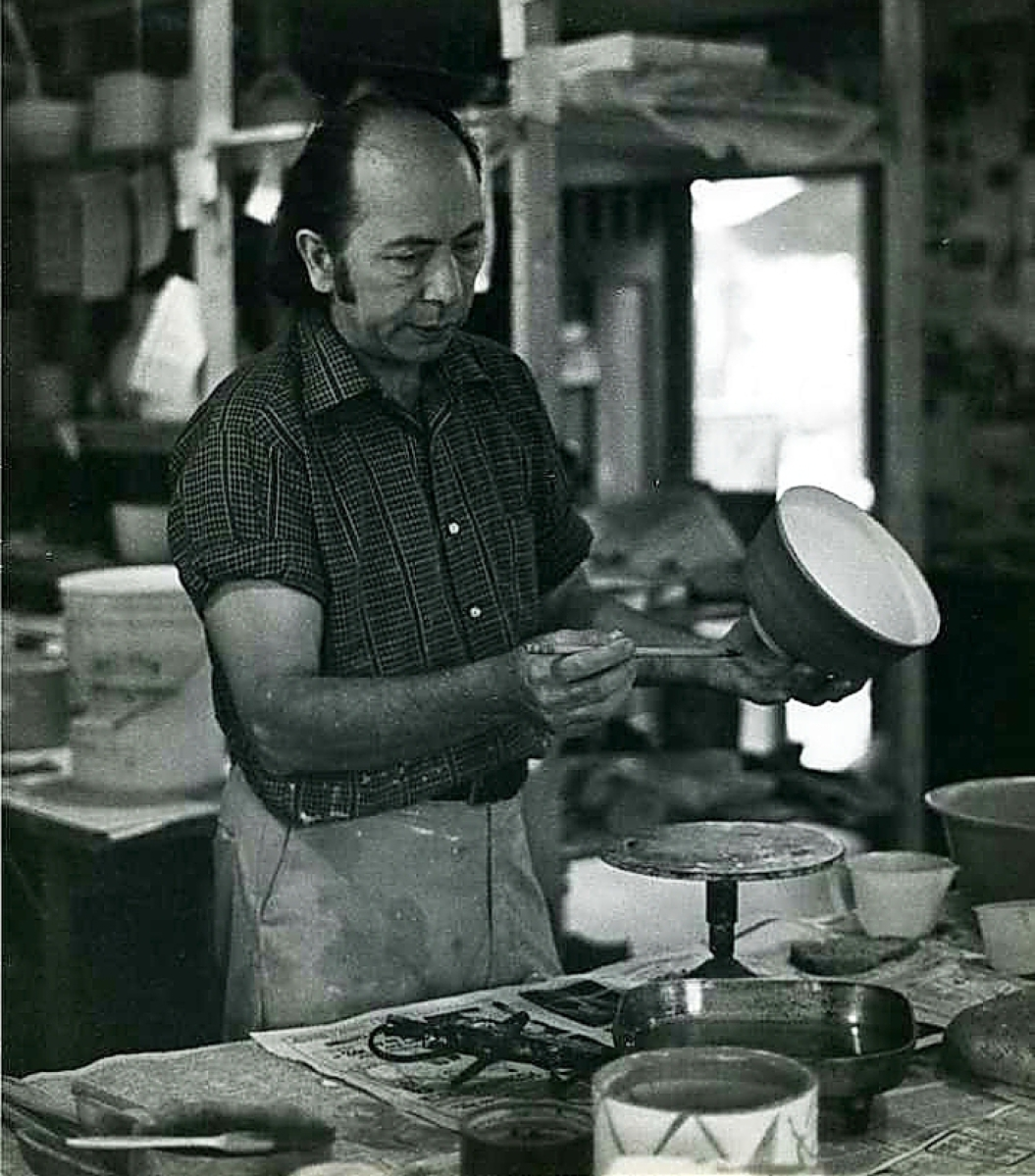 Gerry Williams at work in his studio, decorating a bowl.