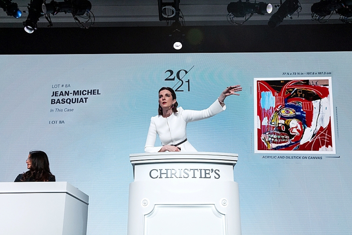 """Gemma Sudlow on the podium at Christie's May 11 Twenty-First Century sale, selling Basquiat's   """"In This Case,"""" which sold for $93.1 million."""