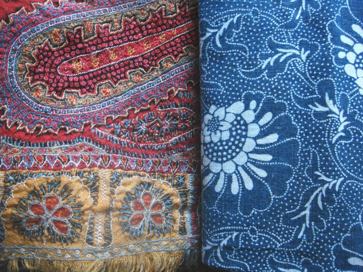 A detail photo of two textiles with Martin Platt, Xanthus Antiques. On the left, a hand-woven and embroidered Kashmir shawl from India, on the right a Japanese stencil-resist indigo. Villanova, Penn.
