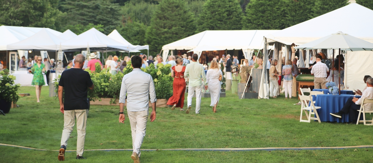 Visitors walk to the back of the field where they are greeted with three dealer tents at the opening night cocktail party.