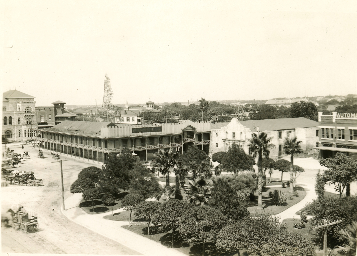 A photograph of Alamo Plaza from approximately 1910, showing the Hugo & Schmeltzer building attached to the Alamo church. Adina Emilia De Zavala Papers, The Dolph Briscoe Center for American History, The University of Texas at Austin.