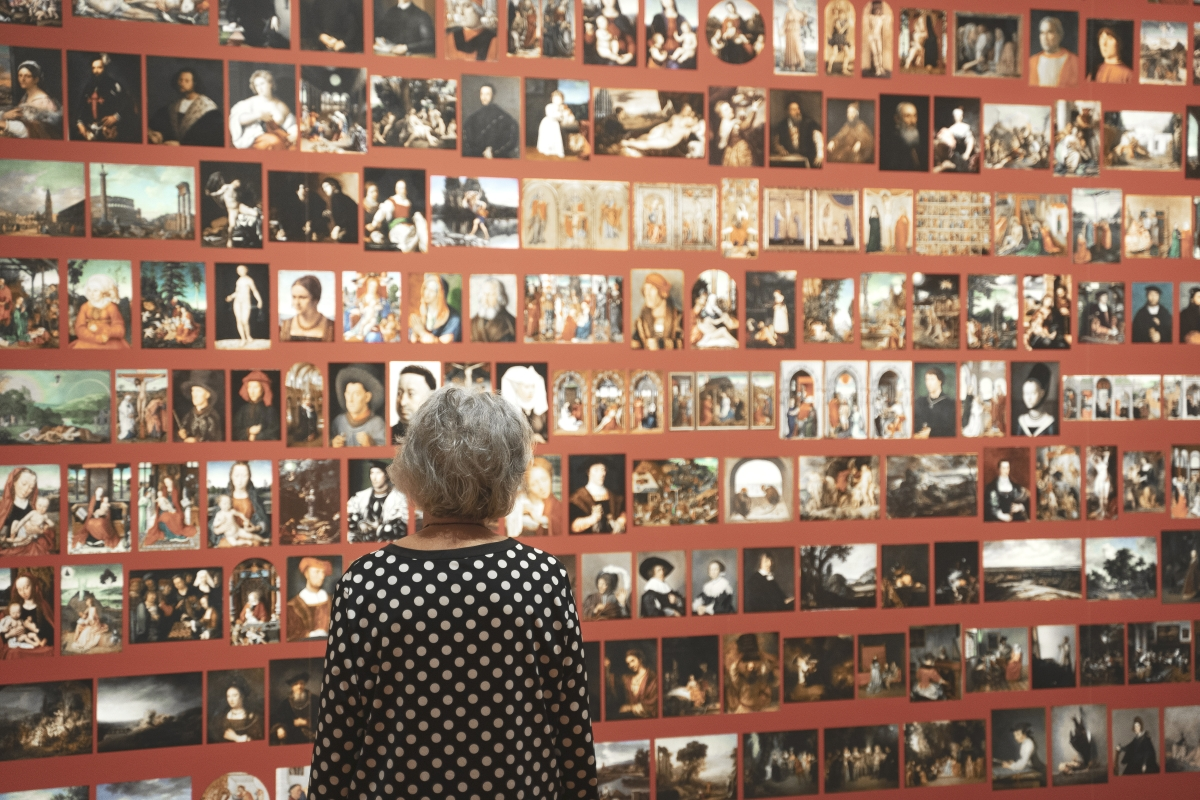 The museum installed a photo collage of The Berlin 202, and here a viewer looks at the snapshots of the many portraits, landscapes and other paintings. Image courtesy Cincinnati Museum of Art.