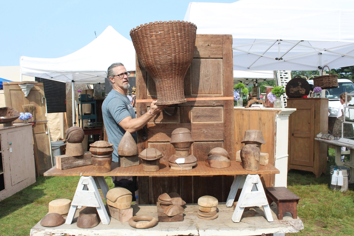 Jeff Mason had to quickly fill a blank space left by a sold item with a French flower market basket that had been sourced from a Maine dealer. Masons Antiques, East Hampton, Mass., also displayed wooden hat forms out of a former Connecticut factory.      —Brimfield Auction Acres