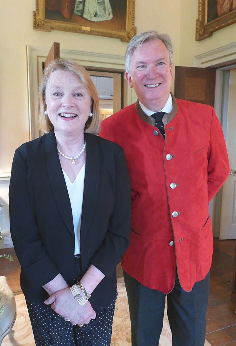 """Lady Clifford of Chudleigh, left, arranged for Savage to meet Downton Abbey's creator, Julian Fellowes. The introduction smoothed the way for Winterthur Museum's blockbuster 2014 exhibition """"The Costumes of Downton Abbey."""" Of the eye-catching jacket, Patrick Baty says, """"Tom is never one to take himself too seriously and has been known to wear what he calls his 'travel mistake' at smart dinners — here a German 'trachten' jacket made of scarlet suede with silver buttons.  So elegant and very envy-making, although I fear that I would never be able to carry it off with as much insouciance."""""""