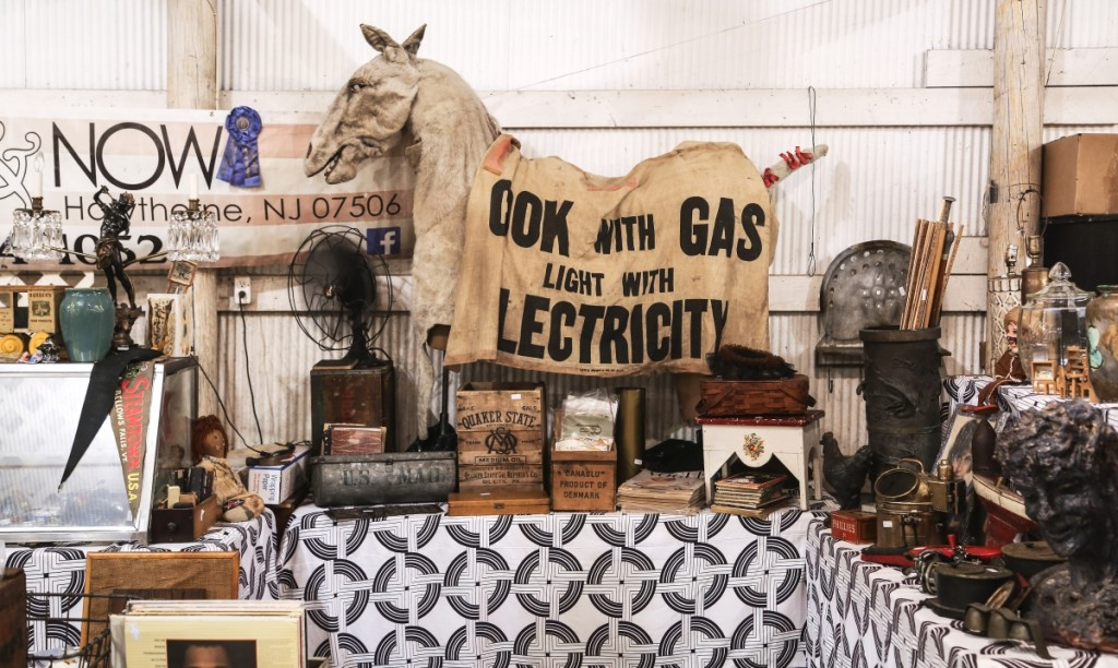 """Then & Now Consignment Shop, Hawthorne, N.J., displayed a vaudeville donkey costume from the 1920s. Draped over it was an advertisement made for a horse that said """"Cook With Gas, Light With Electricity,"""" promoting early electricity use."""