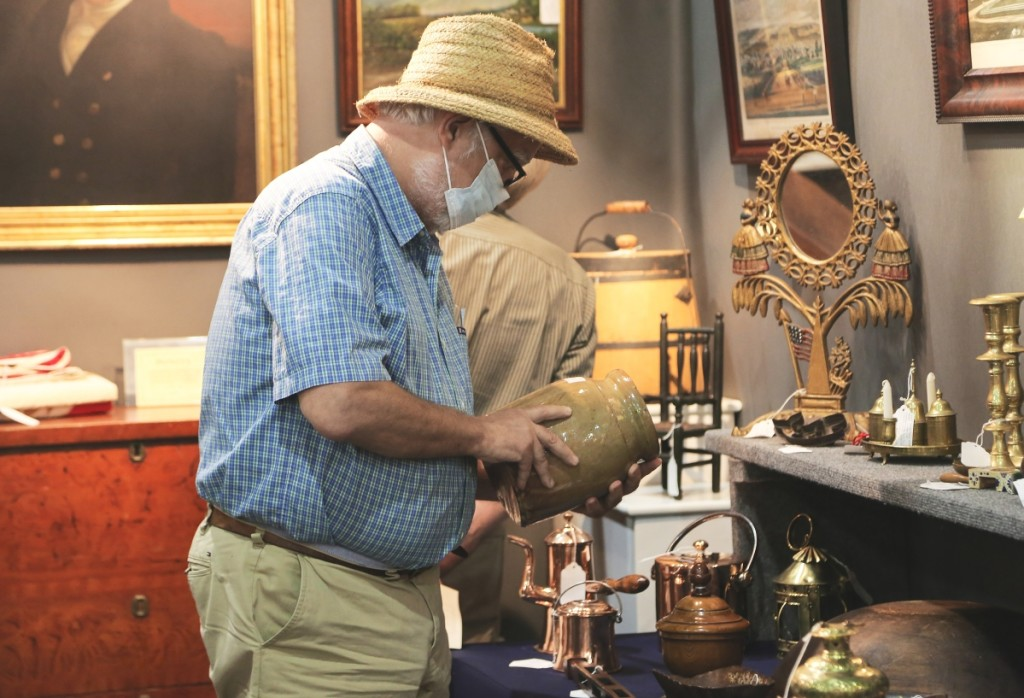A buyer inspects a North Carolina redware jar for sale at Ponzi's Antiques, Trumansburg, N.Y.