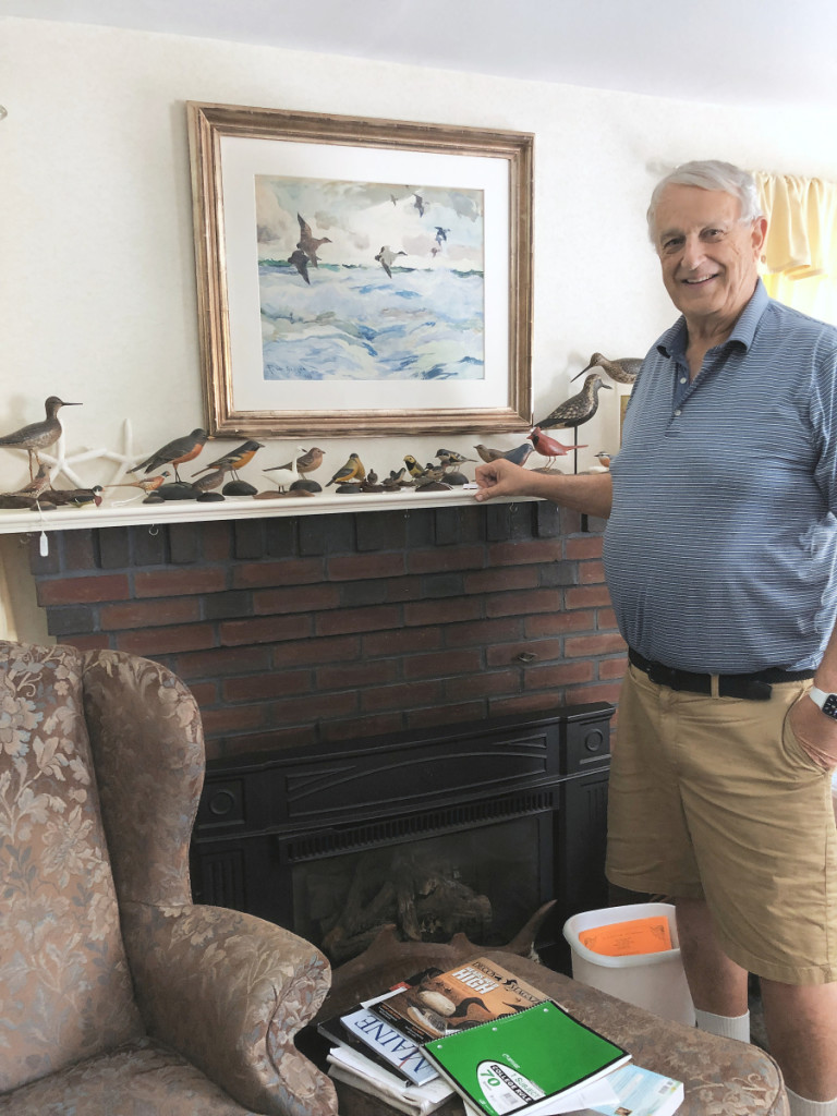 """Ted Harmon in his living room. Some of his miniatures are on the mantel piece and the sporting painting above is a watercolor by Frank Benson. He said, """"I've always wanted a Benson watercolor and now I have one."""""""