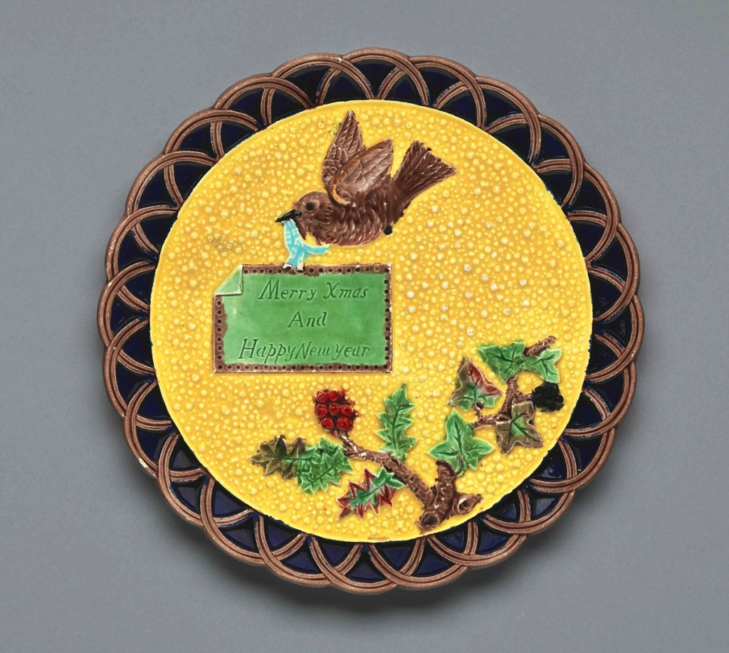 """The Trenton, N.J., factory copied one of its favorite motifs, a bird flying over a flowering plum branch, from the Staffordshire-based firm of Shorter & Boulton. """"Merry Xmas And Happy New Year"""" plate by Eureka Pottery, 1883. Earthenware with majolica glazes, 9½ inches diameter. Private collection, ex collection Dr Howard Silby. Photograph Bruce White."""