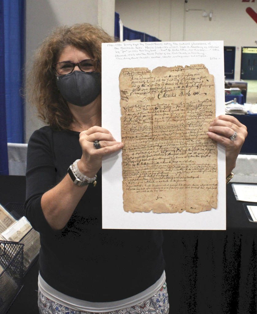 Ann Thorner of Resser-Thorner Antiques, Manchester, N.H., holds up a 1740-80 diary kept by David Merrill noting the natural phenomena of the Merrimac River. Merrill (1708-1782/85) lived in Amesbury. This sheet records weather, comets, earthquakes and eclipses.
