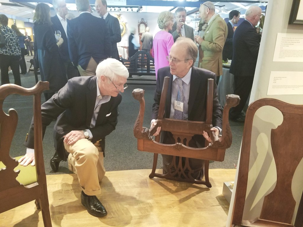Philip showing a Philadelphia Chippendale chair to a customer at the 2019 Philadelphia Antiques Show. Courtesy Lisa Minardi
