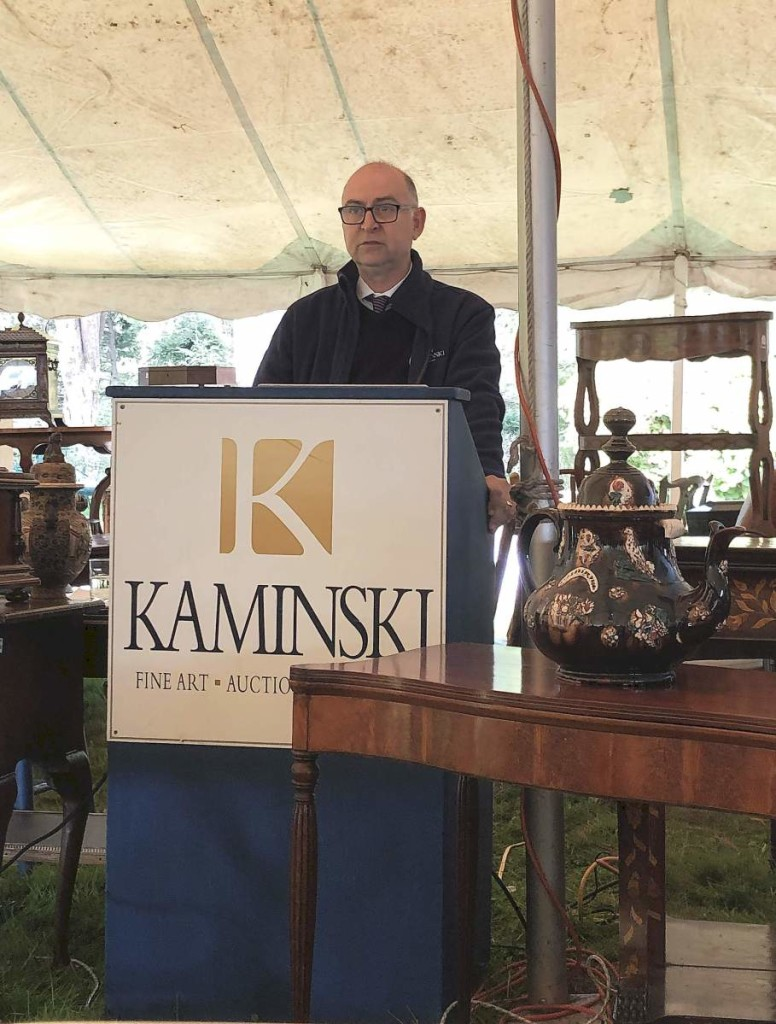 Frank Kaminski at the podium, surrounded by some of the things being sold.
