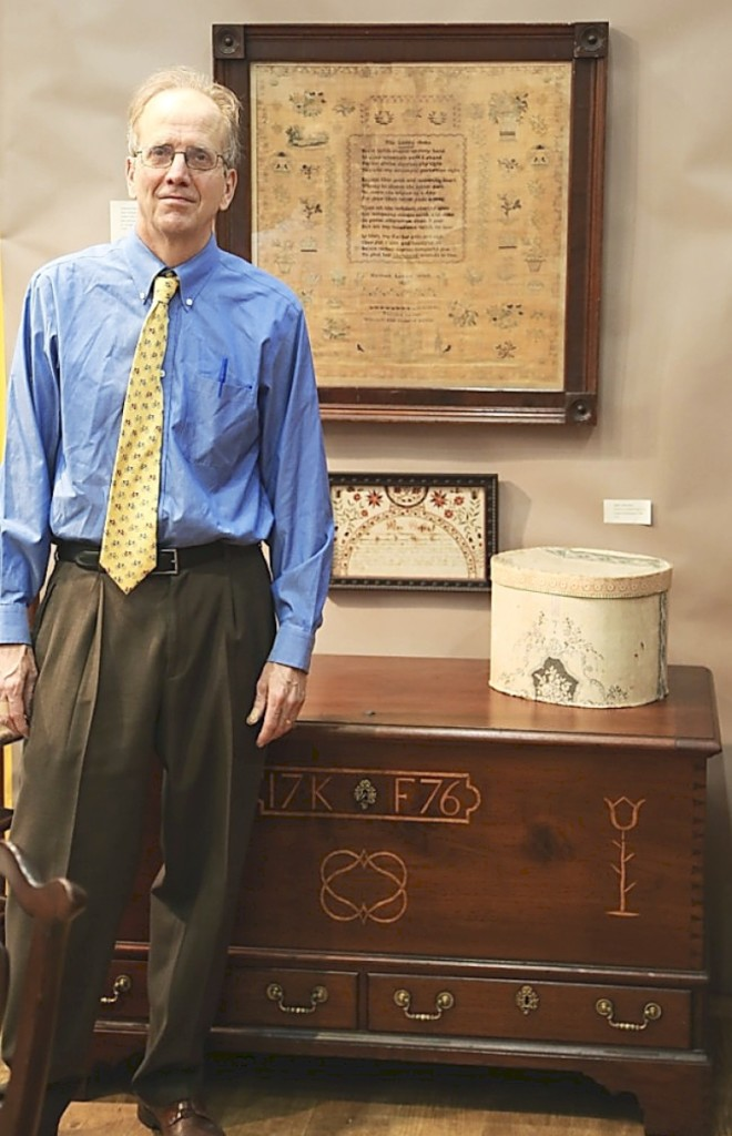 Philip Bradley stands before a 1776 Chester County chest-over-drawers in walnut with mixed-wood inlay. The large 1827 needlework at the top came in its original mahogany frame and was worked by Hannah Levis (1810-1836). Antiques and The Arts Weekly photo.