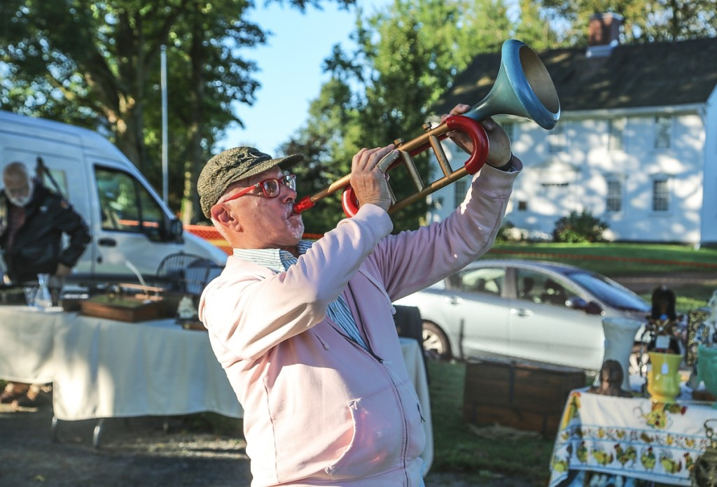 John Gintoff of Gintoff Displays, East Hampton, blows a painted wood trumpet he believes was a store display.