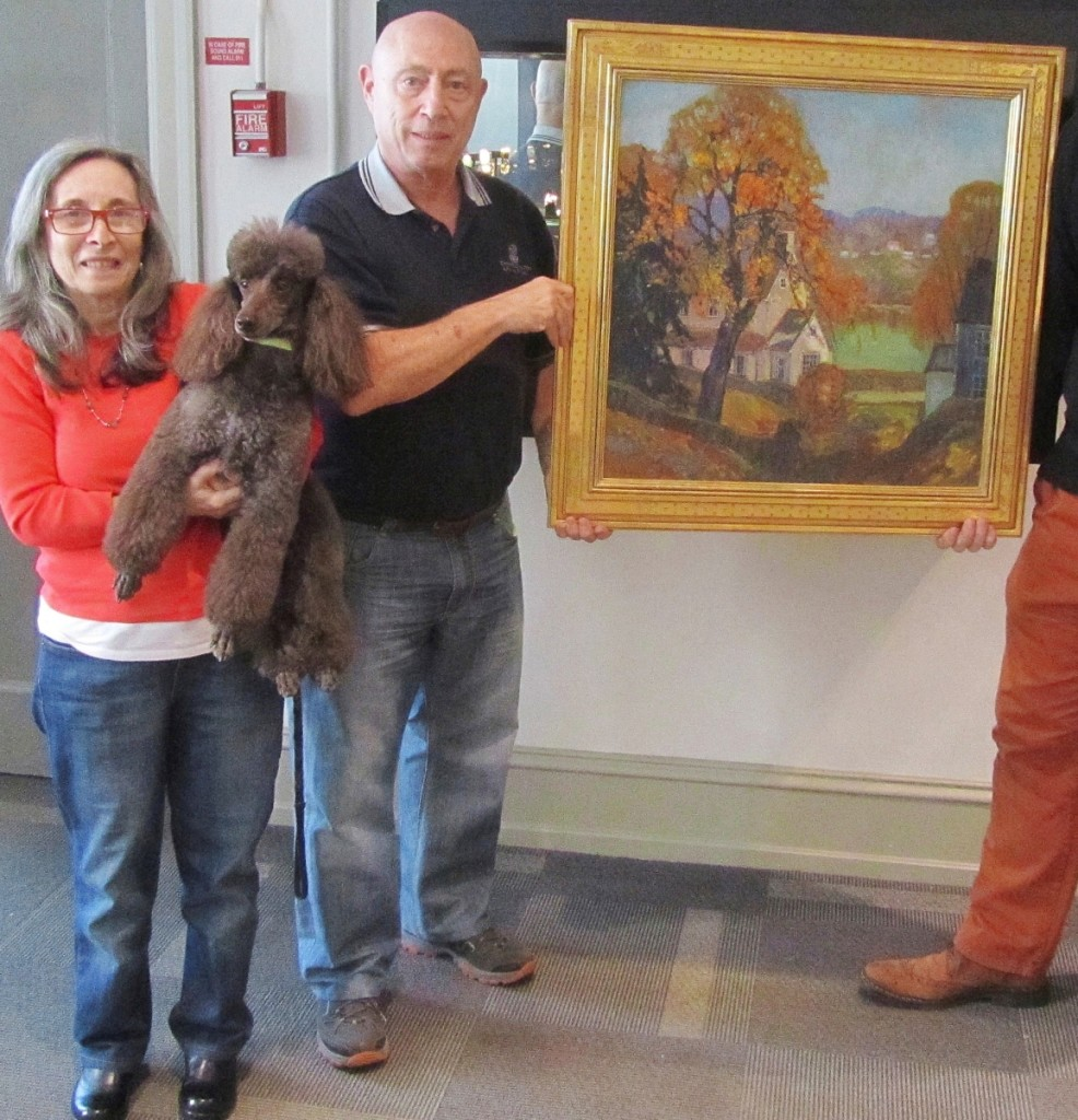 Sue and Les Fox with their miniature poodle, Bruno,   holding a Coppedge painting.